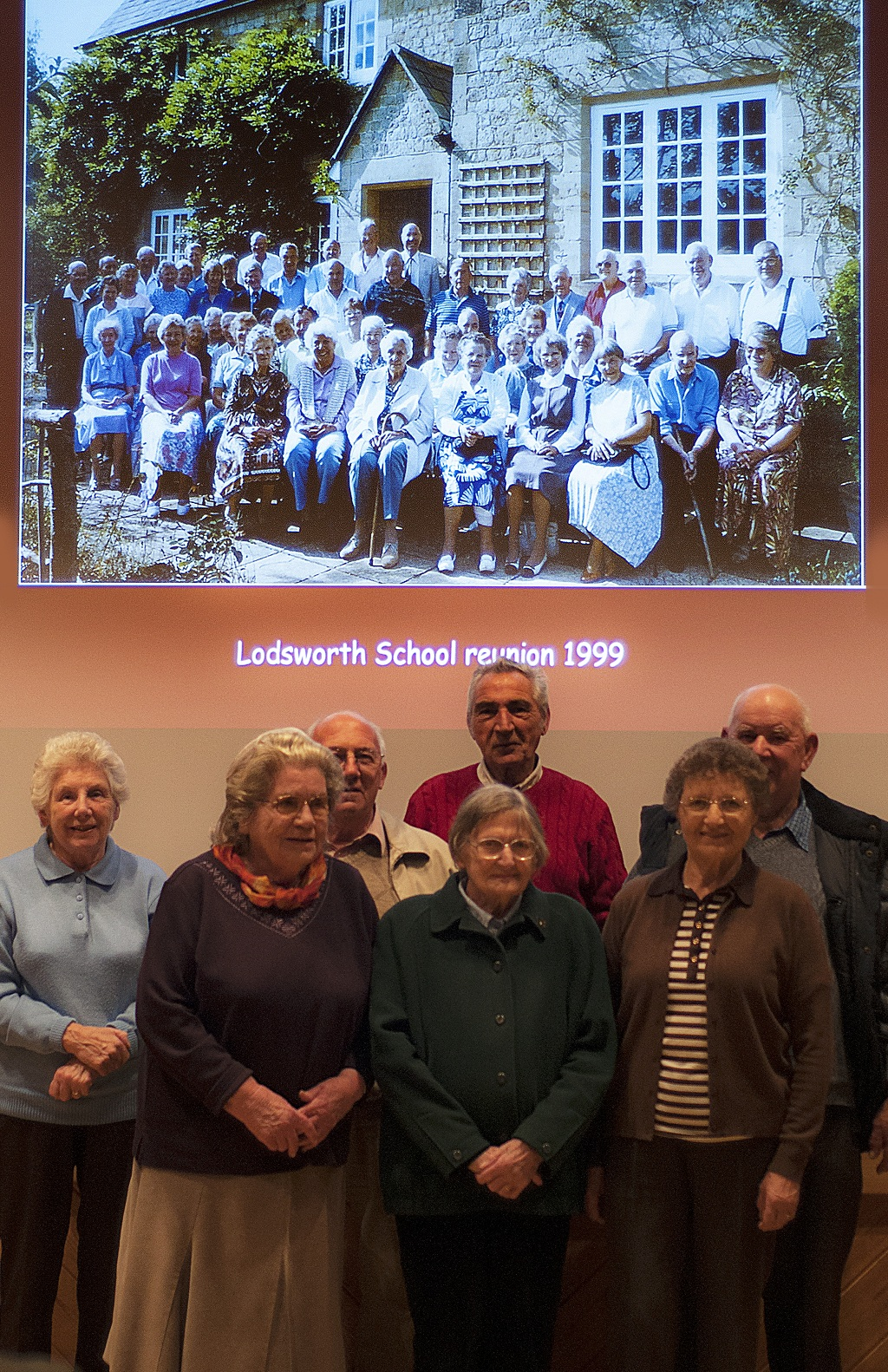 Rosemary Hyde, Sally Hill, John Wakeford, Nellie Brown, Brian Baker, Pauline Enticknap & Ernie Hill, with the backdrop of Stephen Morley's 1999 Lodsworth School reunion photo behind them